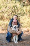 Happy little boy and man walking with dog in the park. Animal concept. Handsome men and cute little boy having fun with doggie in the park outdoors. Happy Royalty Free Stock Images