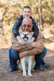 Happy little boy and man walking with dog in the park. Animal concept. Handsome men and cute little boy having fun with doggie in the park outdoors. Happy Royalty Free Stock Photo