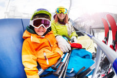 Happy little boy with mom, mountain ski chair lift. Close photo of young women with little boy sitting on chair on ski lift wearing ski mask and helmet smiling Royalty Free Stock Photo