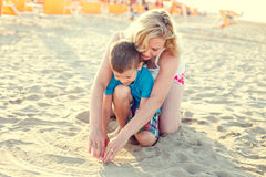 Happy little boy with mother drawing heart into sand Royalty Free Stock Photo