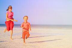 Happy little boy with mother running on beach Royalty Free Stock Photo