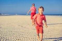 Happy little boy with mother running on beach Royalty Free Stock Images