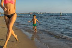 Happy little boy with mother running on summer beach. Positive human emotions, feelings, joy. Funny cute child making vacations an. D enjoying summer Stock Photos