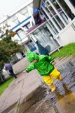 Happy little boy in not getting wet clothes plays in pool on street Stock Photo