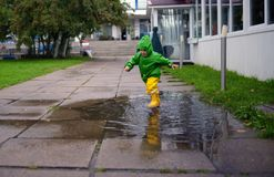 Happy little boy in not getting wet clothes plays in pool on street.  Stock Photo