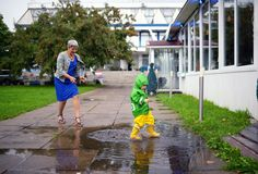 Happy little boy in not getting wet clothes plays in pool on street with grandmother. Happy little boy in not getting wet clothes together with grandmother Stock Image