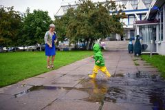 Happy little boy in not getting wet clothes plays in pool on street with grandmother Stock Photos