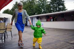 Happy little boy in not getting wet clothes together with grandmother.  Stock Photo