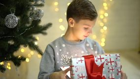 Happy excited little boy opening christmas present gift box surprised in awe sitting near underneath new year tree. Happy little boy opening christmas present stock footage