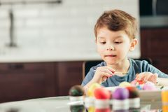 Happy little boy painting Easter eggs, children and creativity royalty free stock photos