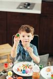 Happy little boy painting Easter eggs, children and creativity stock photos
