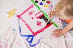 Happy little boy painting on the floor Stock Image
