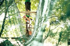 Summer adventure leisure in Albania. Happy little boy passing the cable route high among trees, climbing and playing, extreme sport in adventure park Royalty Free Stock Photo