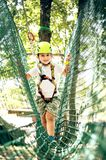 Summer adventure leisure in Albania. Happy little boy passing the cable route high among trees, climbing and playing, extreme sport in adventure park Stock Images