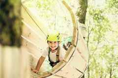Summer adventure leisure in Albania. Happy little boy passing the cable route high among trees, climbing and playing, extreme sport in adventure park Royalty Free Stock Photography