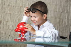 Happy little boy with piggy bank in office Royalty Free Stock Photo