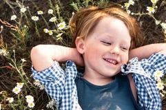 Happy little boy lies in daisy field. Happy little boy in a plaid shirt lies in daisy field royalty free stock image
