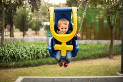 Happy little boy on the playground swing Royalty Free Stock Images