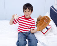 Happy little boy playing baseball in bed Royalty Free Stock Images