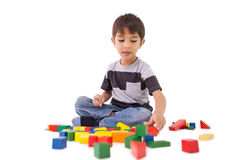 Happy little boy playing with building blocks Stock Photo