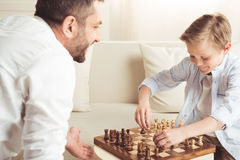 Happy little boy playing chess together with father at home. Side view of happy little boy playing chess together with father at home Royalty Free Stock Image