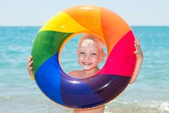 Happy little boy playing with colorful inflatable ring on hot summer day. Child water toys. Children play in tropical resort. Fami royalty free stock photography
