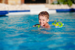 Happy little boy playing with colorful inflatable ring in outdoor swimming pool on hot summer day. Kids learn to swim. Happy little boy with variegated life ring Royalty Free Stock Photography