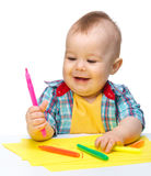 Happy little boy is playing with colorful markers Royalty Free Stock Photo