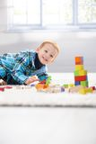 Happy little boy playing with cubes. Happy little boy playing with building cubes at home on floor Royalty Free Stock Image