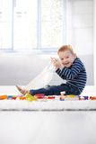 Happy little boy playing on floor. Having cubes and plastic bag Stock Photos