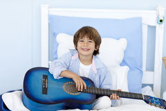 Happy little boy playing guitar in bed Stock Photo