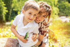 Happy little boy playing with his mother in the city park on a s. Ummer sunny day. Mother and son in the park near pond Royalty Free Stock Image
