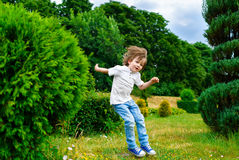 Happy little boy playing and jumping in the park. Outdoors Royalty Free Stock Images