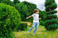 Happy little boy playing and jumping in the park Stock Photography