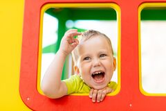 Happy little boy playing on the Playground, boy looking out of the window, children`s lifestyle