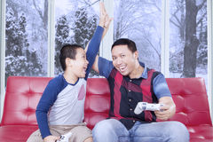 Happy little boy playing playstation with dad. Portrait of joyful little boy winning the video game competition and claps hands with his dad at home Stock Photography