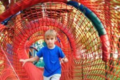 Happy little boy playing in rope tunnel at the modern playground. Summer holidays. Happy and healthy childhood stock images