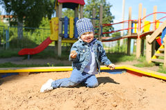 Happy little boy playing with sand on playground Royalty Free Stock Image