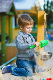 Happy little boy playing in sandbox at playground Royalty Free Stock Photos