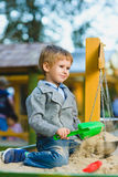 Happy little boy playing in sandbox at playground Stock Images