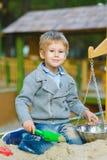 Happy little boy playing in sandbox at playground Stock Photo