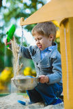 Happy little boy playing in sandbox at playground Stock Image