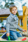 Happy little boy playing in sandbox at playground Stock Photography