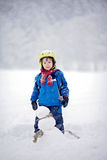 Happy little boy playing in the snow while snowing, helmet. Scarf and gloves Stock Photo