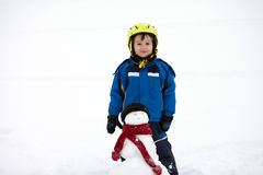 Happy little boy playing in the snow while snowing, helmet Royalty Free Stock Photography