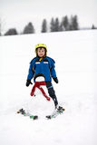 Happy little boy playing in the snow while snowing, helmet Royalty Free Stock Photo