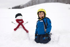 Happy little boy playing in the snow while snowing, helmet Royalty Free Stock Image