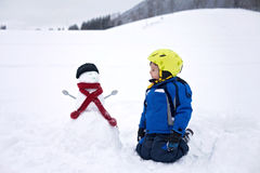 Happy little boy playing in the snow while snowing, helmet Stock Image