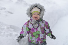 Happy little boy is playing with snow on winer background Royalty Free Stock Images