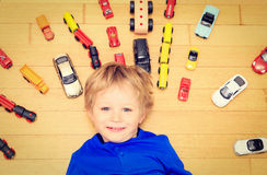 Happy little boy playing with toy cars indoor Royalty Free Stock Photos